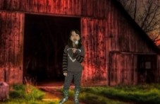 Girl is standing next to a barn, singing